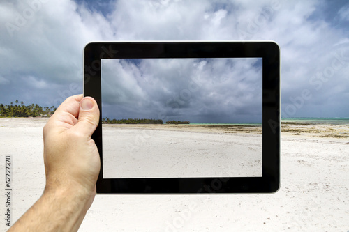 Taking picture with digital tablet of a beach in Zanzibar