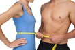 Mid section of a fit man measuring womans waist