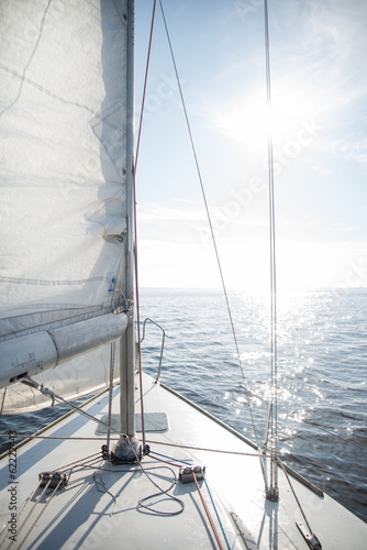 Fototapeta Yacht sailing towards the sunset