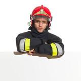 Fireman in red helmet lean on the blank banner