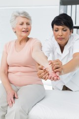 Female physiotherapist examining a senior patients hand