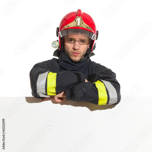 Fireman in red helmet lean on the blank banner - 62222699