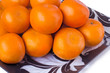 canvas print picture - Large ripe tangerines in a glass dish on a white background.