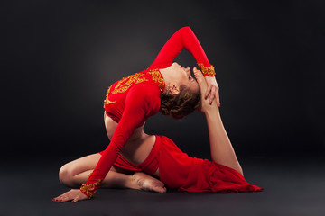Sorgeous sporty woman in red clothing doing yoga exercise