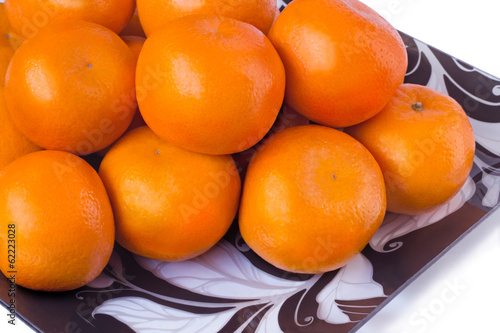 canvas print picture Large ripe tangerines in a glass dish on a white background.