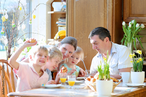 Family with three kids eating eggs during Easter breakfast