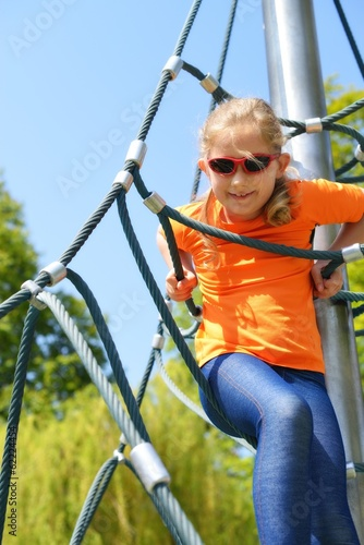 Girl climbing up the ropes.