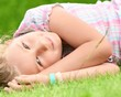 Young girl lying on the grass.