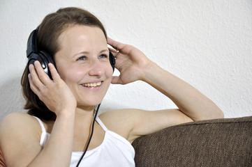Frau lacht und hört Musik
