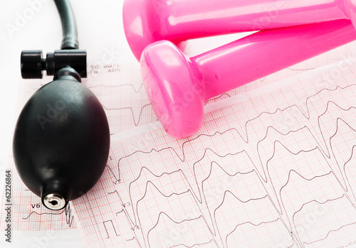 Sphygmomanometer, cardiogram and pink dumbbells