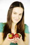 Closeup of fresh strawberries in hands of female model