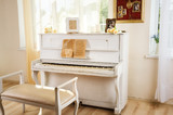 Old white piano in vintage interior