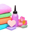 Colorful stacked spa towels, sponges and shampoo bottle