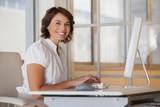 Smiling businesswoman using computer at office desk