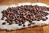 Grains of roasted coffee on linen napkin on wooden table