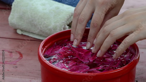 woman throws small petals in bowl immerse your hands in water