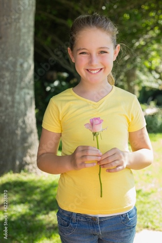 Girl holding flower in park