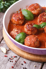 hot meatballs with tomato sauce and basil in a pan