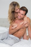 Loving young woman embracing man from behind