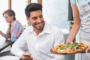 Waitress giving pizza to a man at coffee shop