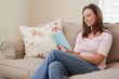 Smiling woman reading book in living room