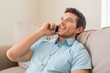 Relaxed man using mobile phone in living room