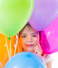 Happy child holding bunch of air balloons