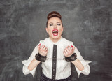 Screaming business woman with handcuffs on her hands
