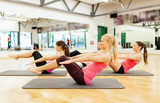 group of smiling women exercising on mats in gym