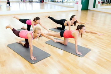 group of smiling women stretching on mats in gym