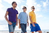 group of male friends walking on the beach