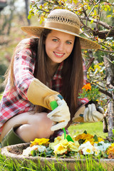 Beautiful young woman smiles to camera with flower in hand