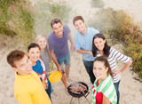 group of friends making barbecue on the beach