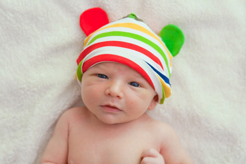 Little baby naked in a bed with colorful hat