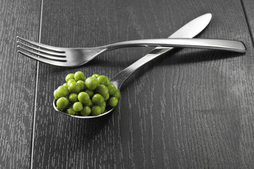 Green peas in the spoon and fork on the dark wooden table