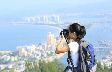 woman photographer taking photo on seaside mountain peak