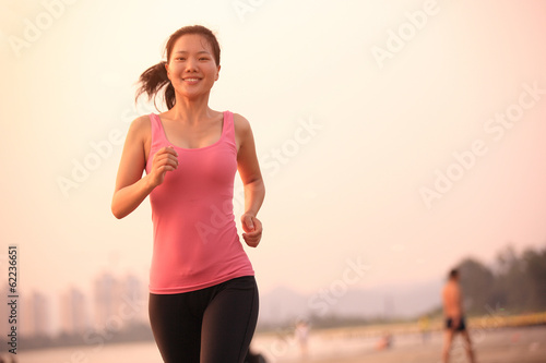 woman runner running at beach