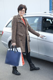Woman with shopping bags next car
