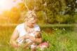 Mutter beim Stillen von  Baby auf Wiese
