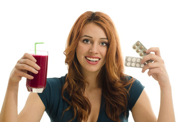Woman choosing between vitamin pills and an organic smoothie