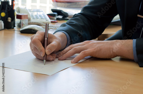 Man writes something on a white paper. Office work