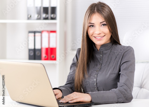 Businesswoman in the office, sitting with laptop