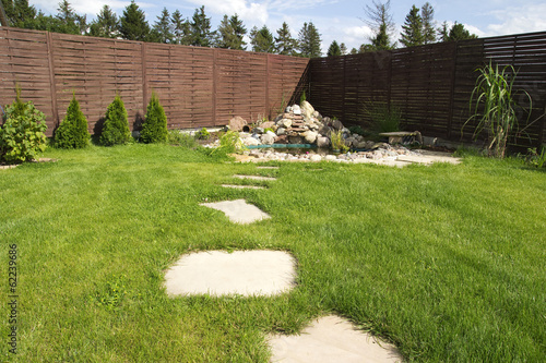 backyard surrounded by wooden fence - 62239686