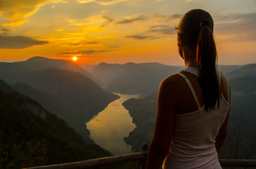 Girl watching sunset from the top of the mountain