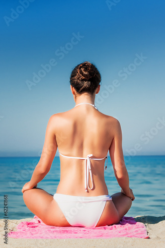 Young girl practicing Yoga at the beach