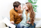 Young anxious couple quarrels by consulting their bank account
