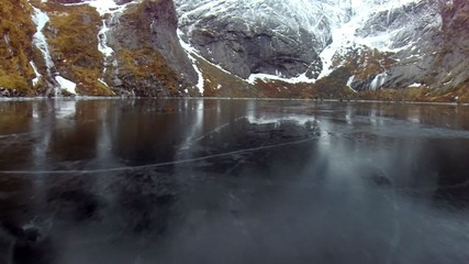 Flying above frozen lake near fjords in Norway