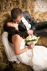 portrait of beautiful bride and groom kissing on stack of hay