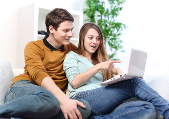Attractive joyful woman showing something on its laptop computer