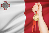 Medal in hand with flag on background - Republic of Malta